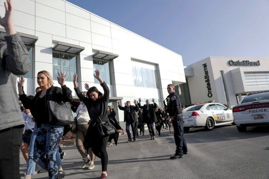 People evacuate after a reported shooting at Fashion Place Mall in Murray, Utah, on Sunday.
