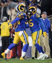 Los Angeles Rams running back Todd Gurley (30) celebrates running back C.J. Anderson (35) after scoring a touchdown against the Dallas Cowboys in the first half in a NFC Divisional playoff football game at Los Angeles Memorial Coliseum.