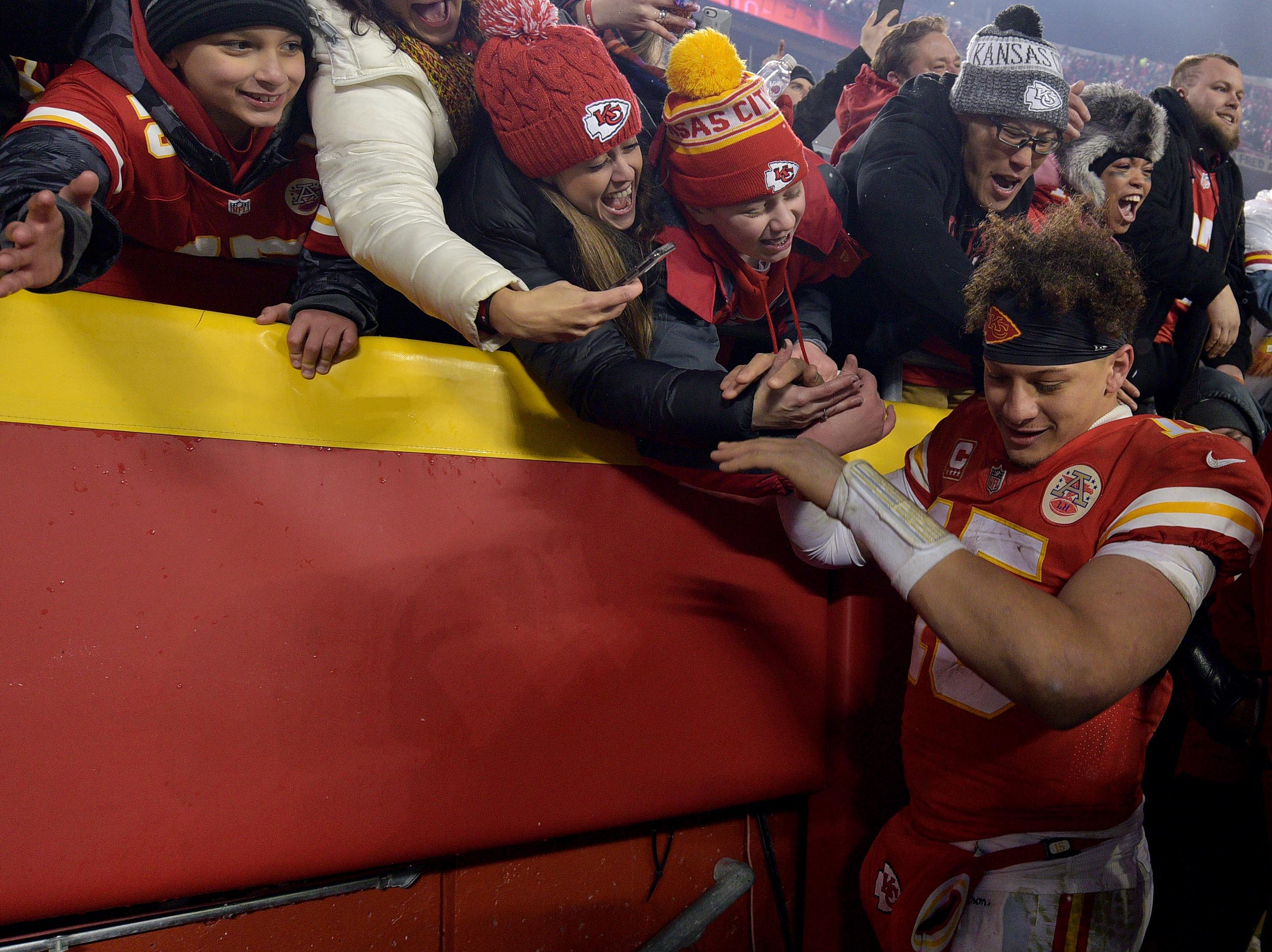 Kansas City Chiefs quarterback Patrick Mahomes (15) high-fives fans after beating the Indianapolis Colts at Arrowhead Stadium.