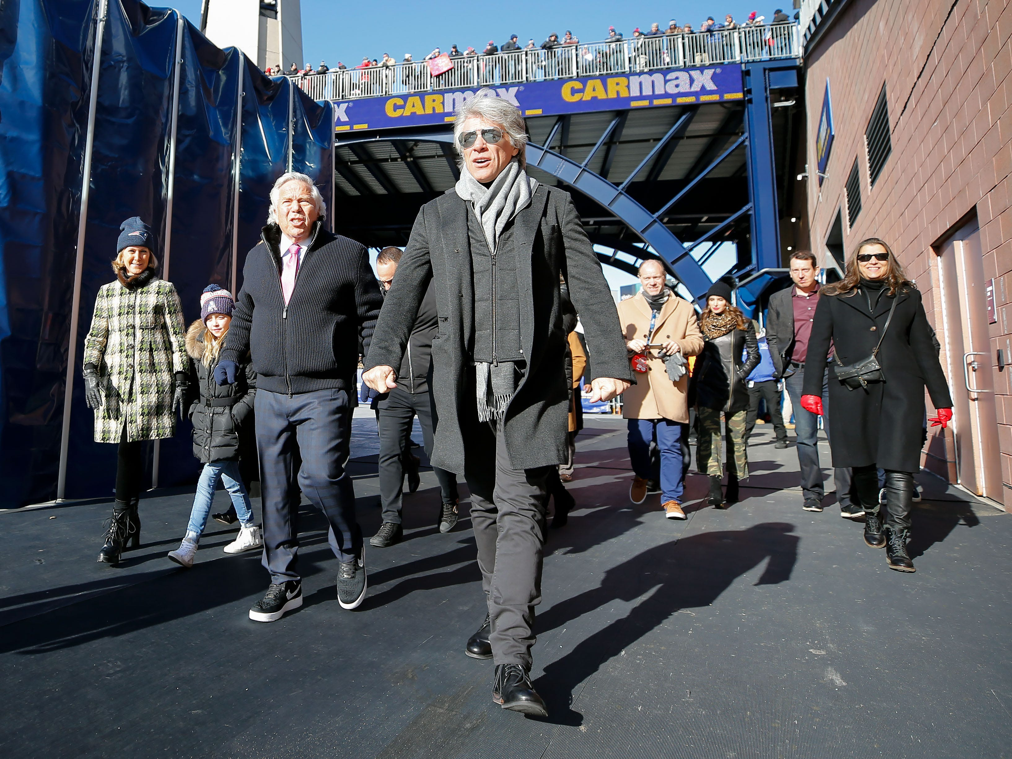 New England Patriots owner Robert Kraft and singer Bon Jovi walk onto the field during warmups before a game against the Los Angeles Chargers in an AFC Divisional playoff football game at Gillette Stadium.