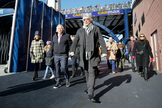 New England Patriots owner Robert Kraft and Jon Bon Jovi walk onto the field during warmups at the Patriots-Los Angeles Chargers AFC Divisional playoff football game at Gillette Stadium.