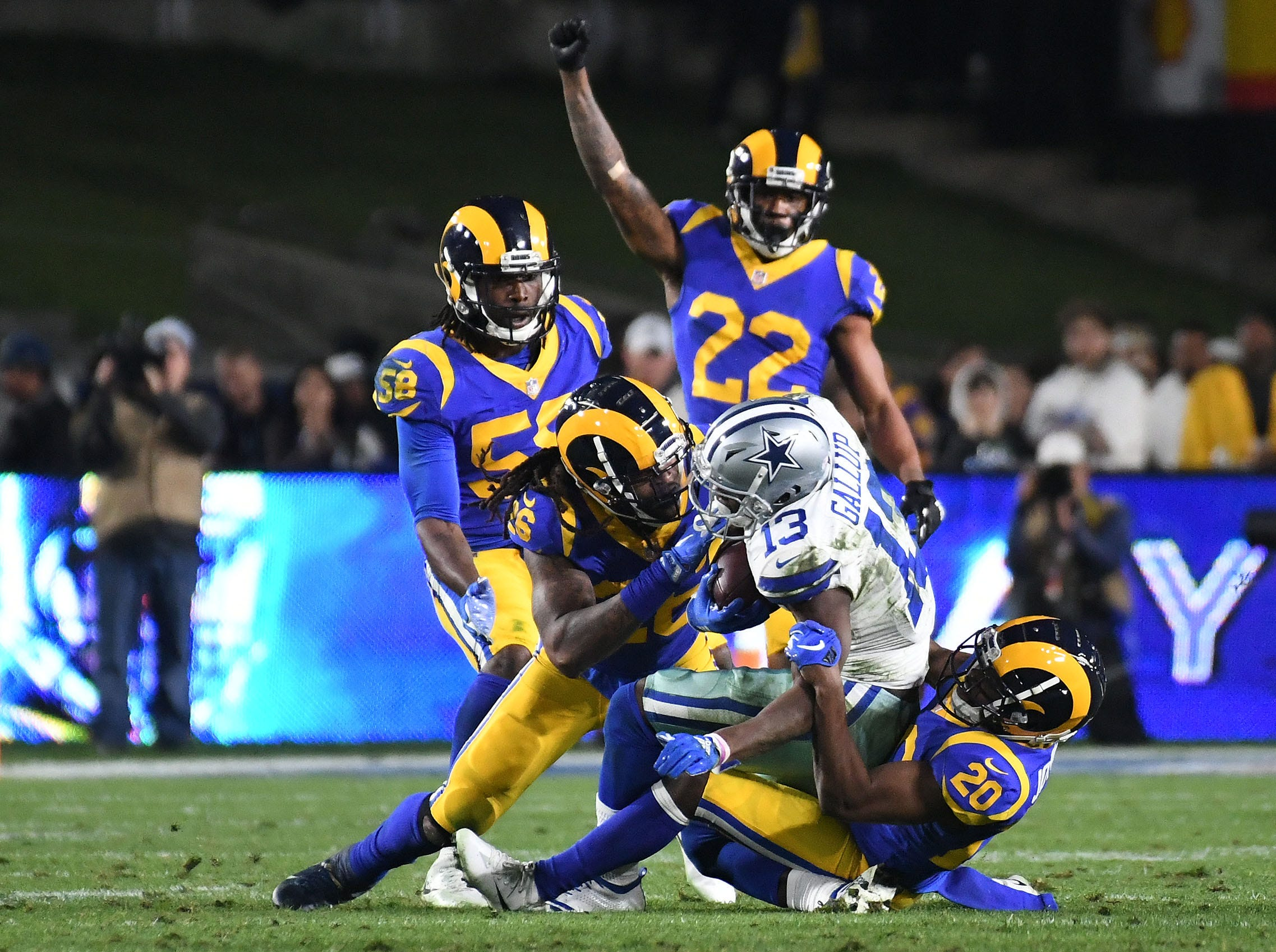 The Los Angeles Rams' Mark Barron (26) and Lamarcus Joyner (20) tackle Dallas Cowboys wide receiver Michael Gallup (13) in the third quarter at the Los Angeles Memorial Coliseum.