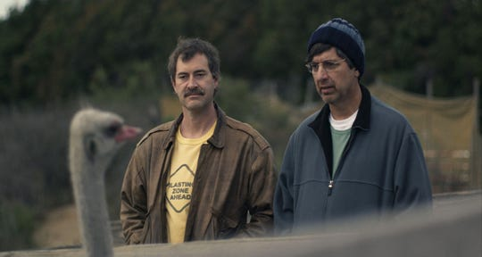 "Mark Duplass (left) and Ray Romano play friends who go on a road trip after a cancer diagnosis in the Netflix comedy-drama ""Paddleton."""