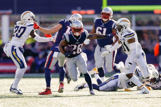 New England Patriots running back James White (28) runs against Los Angeles Chargers defensive back Adrian Phillips (31) during the first quarter in an AFC Divisional playoff football game at Gillette Stadium.