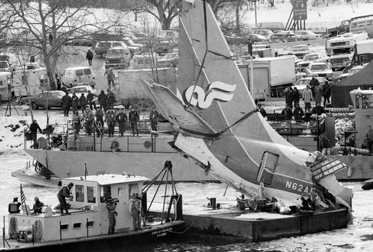 The tail section of the Air Florida jetliner that crashed into the Potomac River after hitting the 14th Street Bridge is hoisted onto a barge in the river on Jan. 17, 1982, four days after the incident.