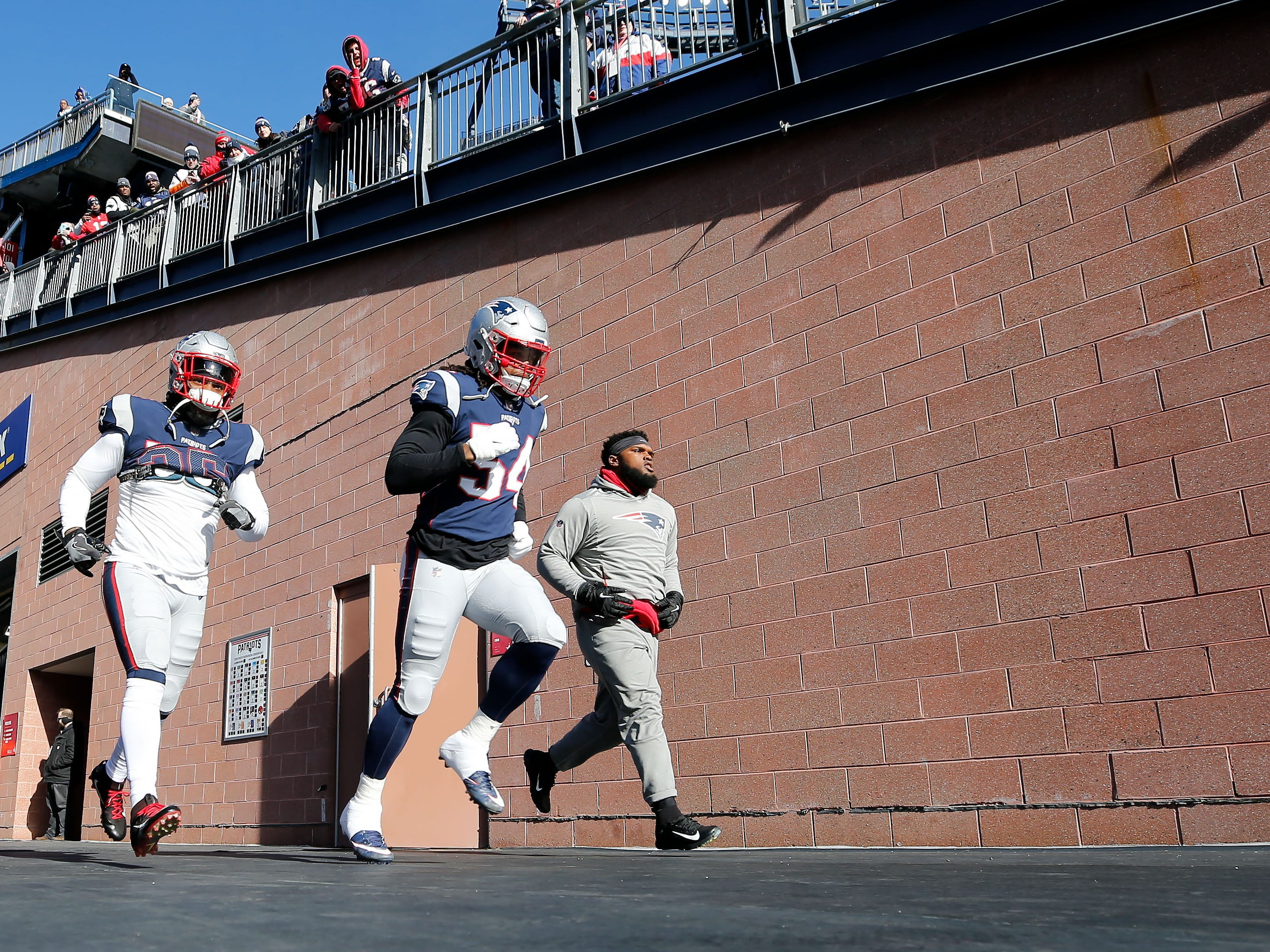 New England Patriots outside linebacker Dont'a Hightower (54) and defensive back Keion Crossen (35) walk onto the field for warmups before a game against the Los Angeles Chargers in an AFC Divisional playoff football game at Gillette Stadium.