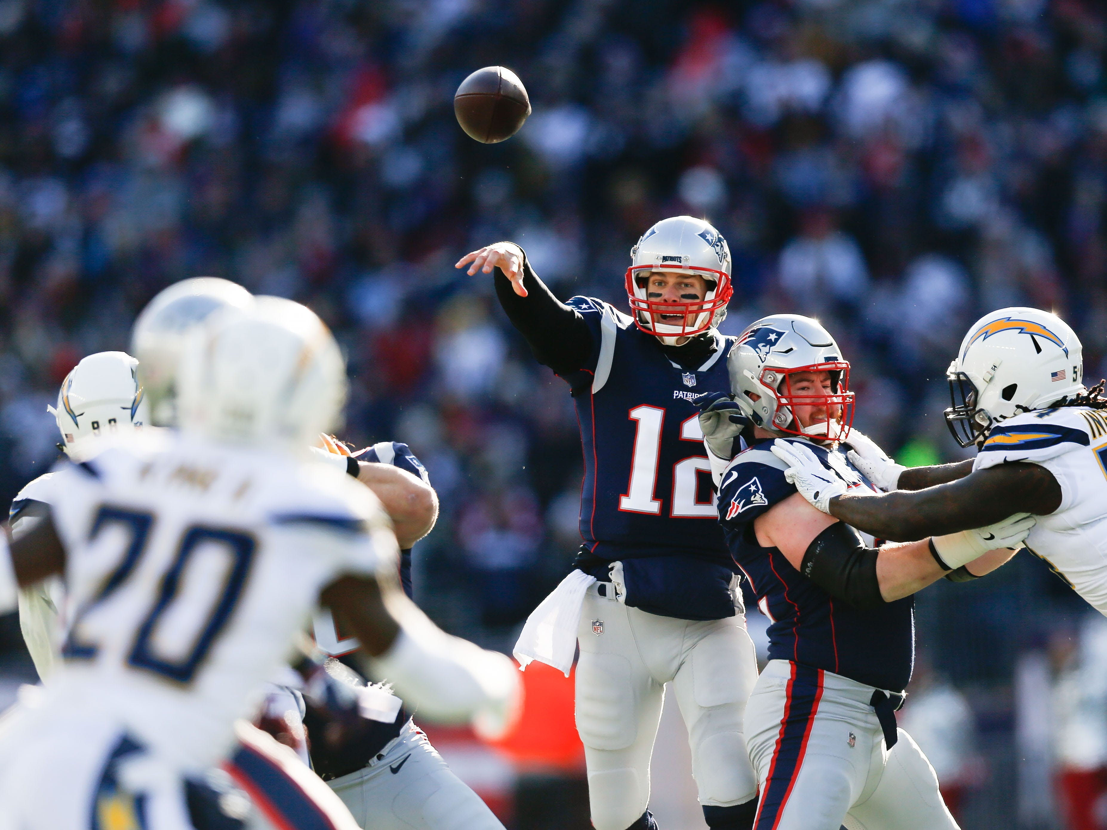 New England Patriots quarterback Tom Brady (12) throws against the Los Angeles Chargers during the first quarter in an AFC Divisional playoff football game at Gillette Stadium.