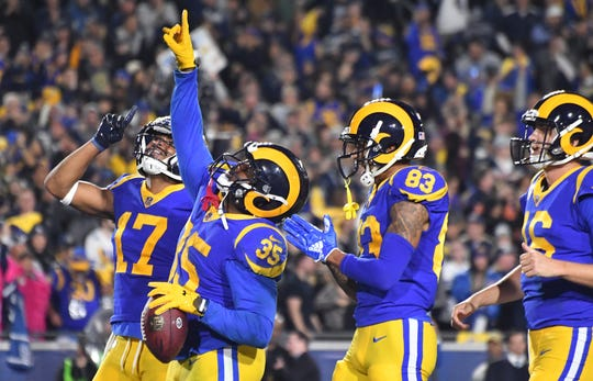 Los Angeles Rams running back C.J. Anderson (35) celebrates with wide receiver Josh Reynolds (83) and wide receiver Robert Woods (17) after scoring a touchdown against the Dallas Cowboys in second quarter in a NFC Divisional playoff football game at Los Angeles Memorial Stadium.