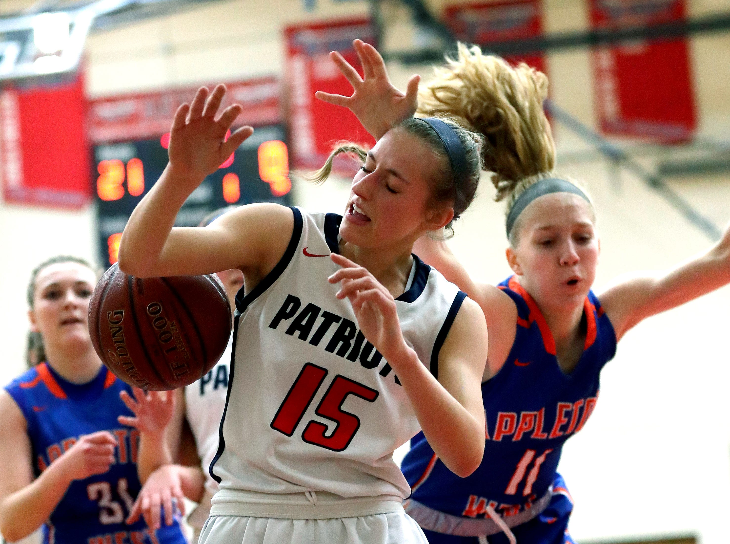 Appleton East High School's Meghan Borowski (15) and Appleton West High School's Jamie Winsted (11) collide under the basket during their girls basketball game Friday, January 11, 2019, at Appleton East High School in Appleton, Wis. 