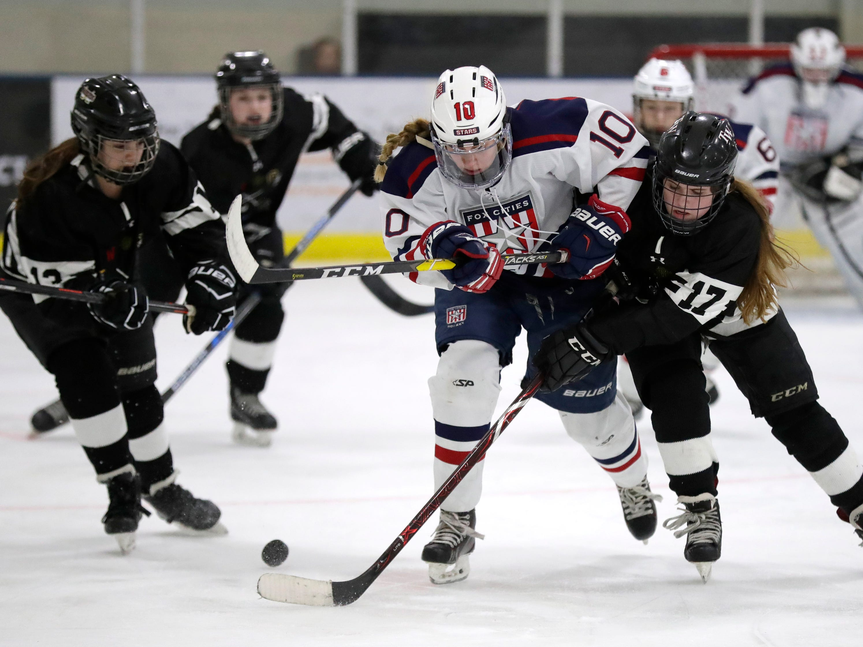 Fox Cities Stars' Madelynn Jablonski (10) battles for control of the puck against the Warbirds' Hattie Verstegen (17) during their girls hockey game Thursday, January 10, 2019, at Tri-County Ice Arena in Fox Crossing, Wis. 