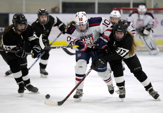 Fox Cities Stars' Madelynn Jablonski (10) battles for control of the puck against the Warbirds' Hattie Verstegen (17) during their girls hockey game Jan. 10 at Tri-County Ice Arena in Fox Crossing.