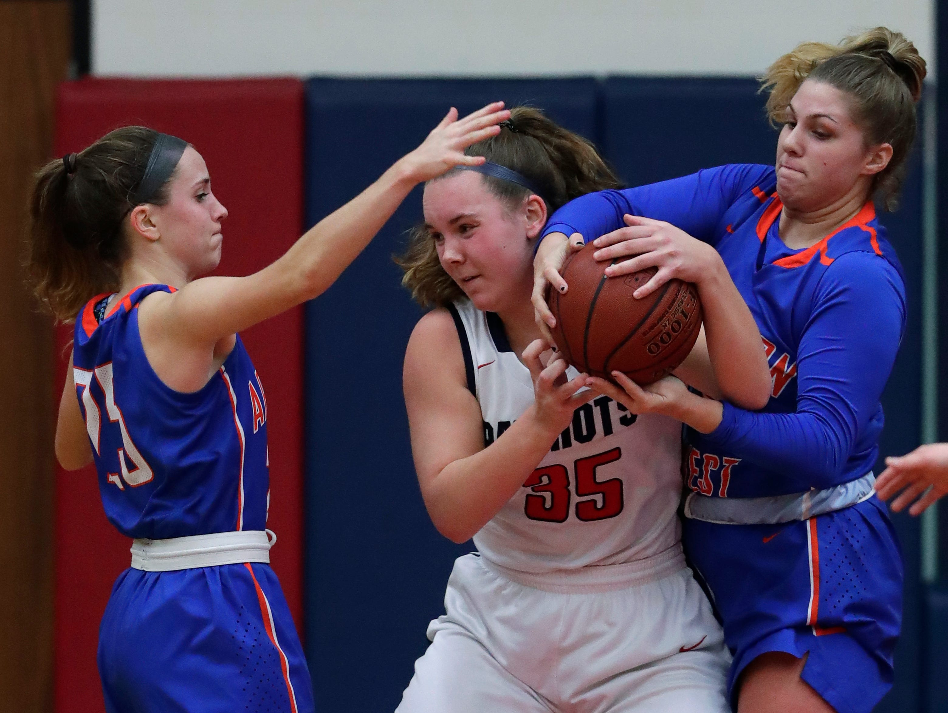 Appleton East High School's Lily Wendland (35) battles for a rebound against Appleton West High School's Julia Smith (25) and Sydney Gehl (35) during their girls basketball game Friday, January 11, 2019, at Appleton East High School in Appleton, Wis. 