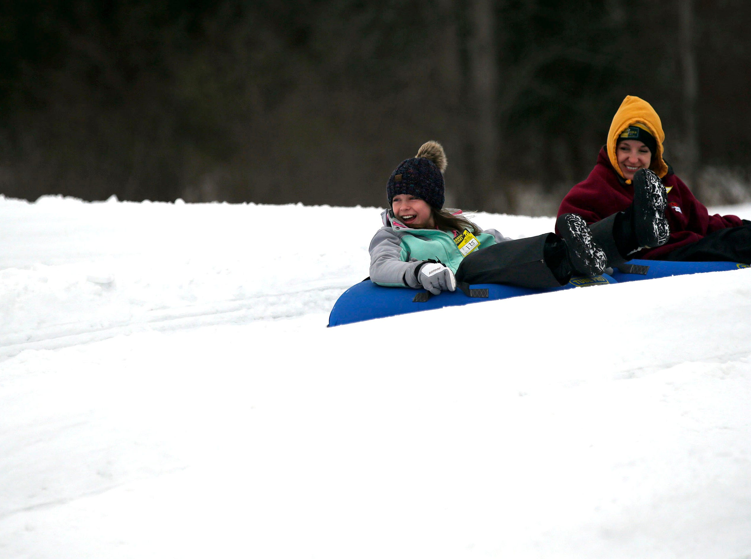 Jennifer Kohnke, center, of Montello and her children Saydee and Klay make a run as a mild winter day brings tubing fans to Nordic Mountain Sunday, January 13, 2019, near Wild Rose, Wis.