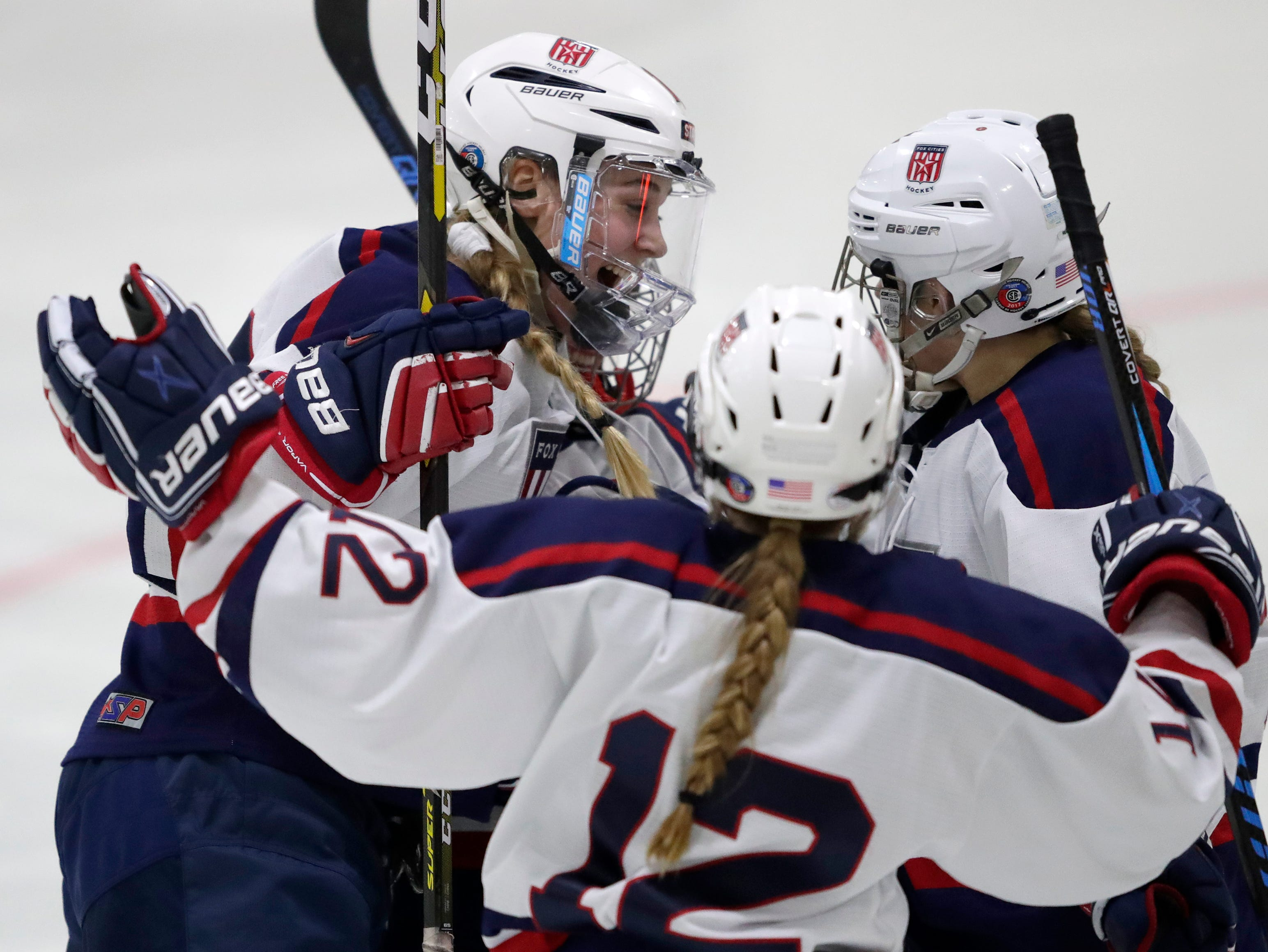 Fox Cities Stars' Madelynn Jablonski (10), Annika Horman (12) and Sarah Marvin (21) celebrates after Marvin scored a goal against the Warbirds during their girls hockey game Thursday, January 10, 2019, at Tri-County Ice Arena in Fox Crossing, Wis. 