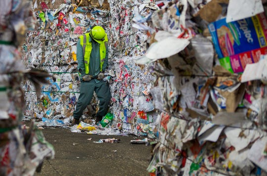 This photo taken Monday, Nov. 19, 2018, shows a Waste Management employee removing a plastic laundry detergent bottle that made it through the sorting process from a bale of mixed paper that is being prepared to be loaded onto a truck at the company's facility on Gasmer Drive in southwest Houston. ( Mark Mulligan/Houston Chronicle via AP)