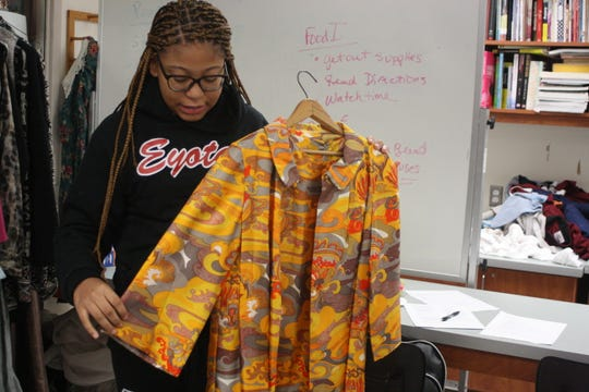 Johnson City High School freshman Josie Dure, 14, holds up a vintage dress and jacket that will be featured in the school's upcoming fashion show and clothing sale. Dure is in charge of the show's purses, ticketing and models.