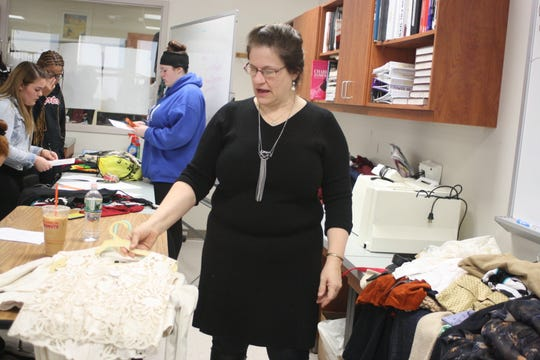Jane Halladay pulls out vintage clothing items to show to her Our World of Fashion class at Johnson City High School.