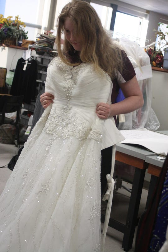 Johnson City High School student Geraldine Molyneaux holds up a wedding dress that will be used in the school's upcoming fashion show and clothing sale.
