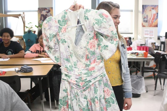 Johnson City high school freshman Erica Cioci holds up a 1980s style dress that will be featured in the school's fashion show and clothing sale. Cioci is the show's secretary and is also in charge of the medium section.