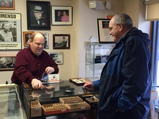 Ron Ortiz, right, of Gilbert, Arizona, buys cigars from Howie Weisburgh at Howie's Humidor in South Burlington on Monday, Jan. 14, 2019.