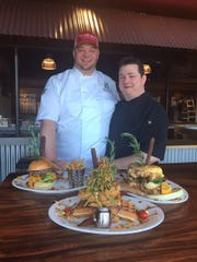 Hash House a Go Go's corporate Executive Chef Spencer Harries, left, and Moorestown location Executive Chef Matt Geraghty show off three of the more popular dishes from the restaurant, which opens its first New Jersey location at Moorestown Mall on Thursday.