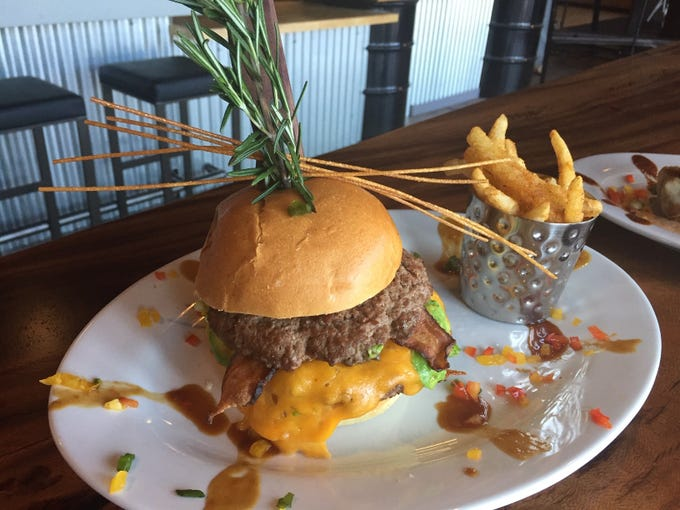 Cheeseburgers at Hash House a Go Go come stuffed with double patties, garnished here with crispy pasta and signature rosemary stalk.