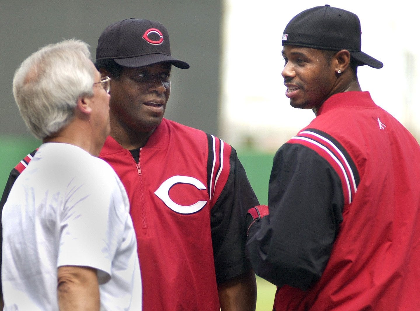 Text: 2001.0615.10.1--REDS RETURN--Ken Griffey, Jr., talks with Reds broadcaster Marty Brennaman as Ken Griffey, Sr. listens during batting practice Friday, June 15. Barry Larkin, Ken Griffey, Jr., and Aaron Boone returned to the lineup at Cinergy Field. The Reds have been plagued by injuries all season, and the trio's return brings new hope to a struggling ball club. Photo by Craig Ruttle/Cincinnati Enquirer