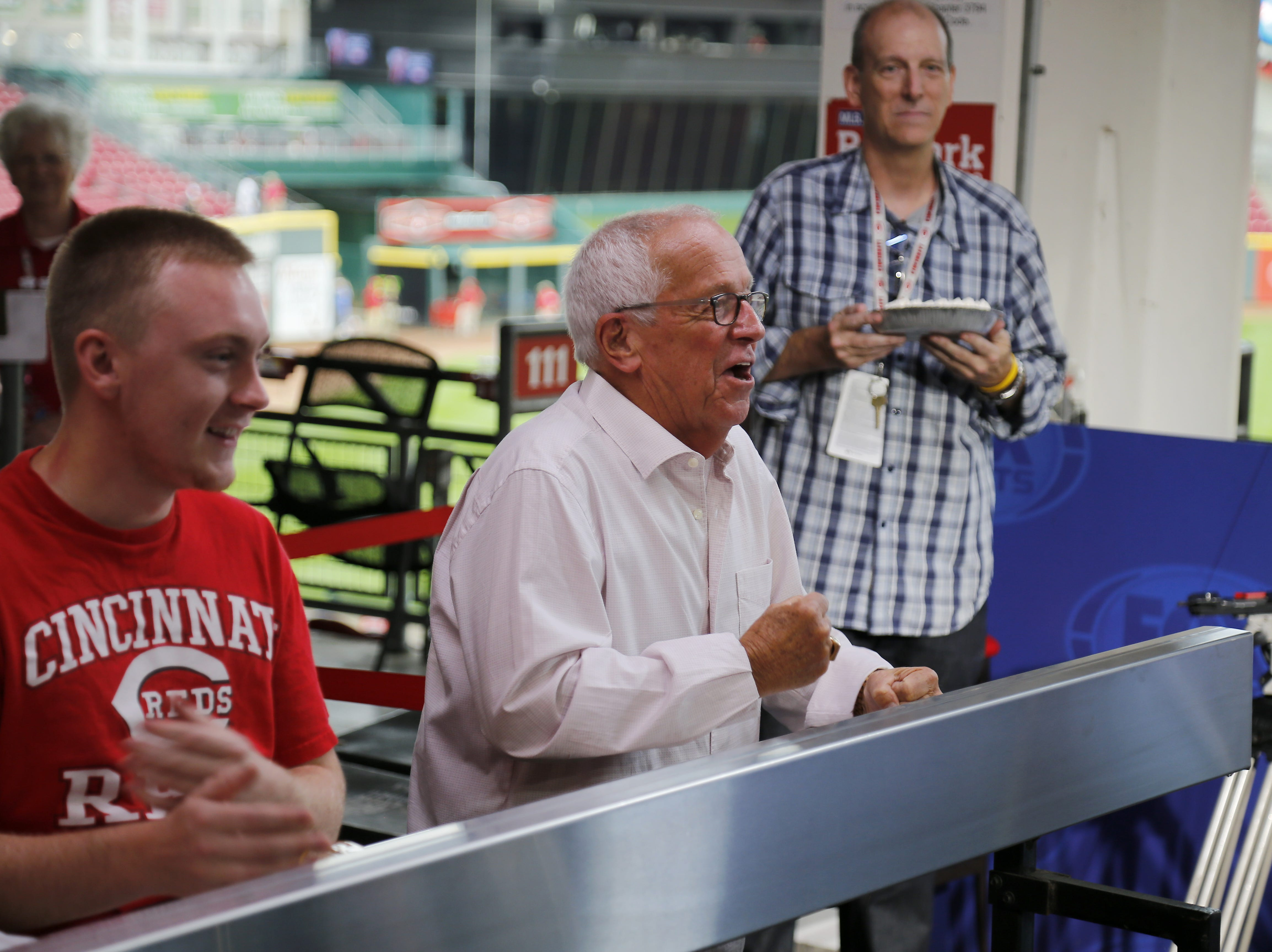 Reds broadcaster Marty Brennaman cheers before his partner Jeff Brantley receives a pie in the face from Jeff Piecoro before the MLB Interleague game between the Cincinnati Reds and the Kansas City Royals at Great American Ball Park in downtown Cincinnati on Tuesday, Sept. 25, 2018.