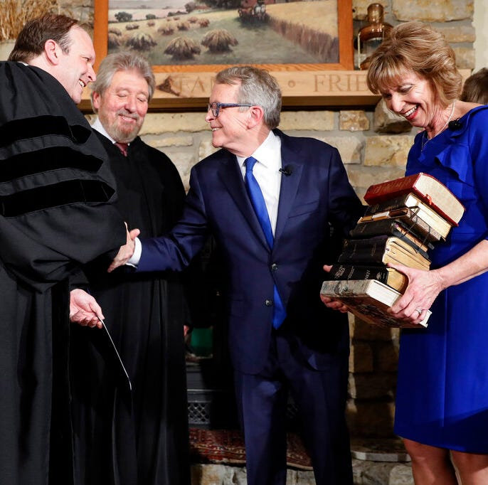 Mike DeWine, center right, is sworn in as the 70th governor of Ohio alongside his wife Fran, right, son and Ohio Supreme Court Justice Patrick DeWine, left, and Judge Thomas Rose of the U.S. District Court Southern District of Ohio, center left, Monday, Jan. 14, 2019, in Cedarville, Ohio. The former U.S. senator took his oath in a private midnight ceremony at his Cedarville home ahead of a public inauguration planned Monday at the Statehouse.