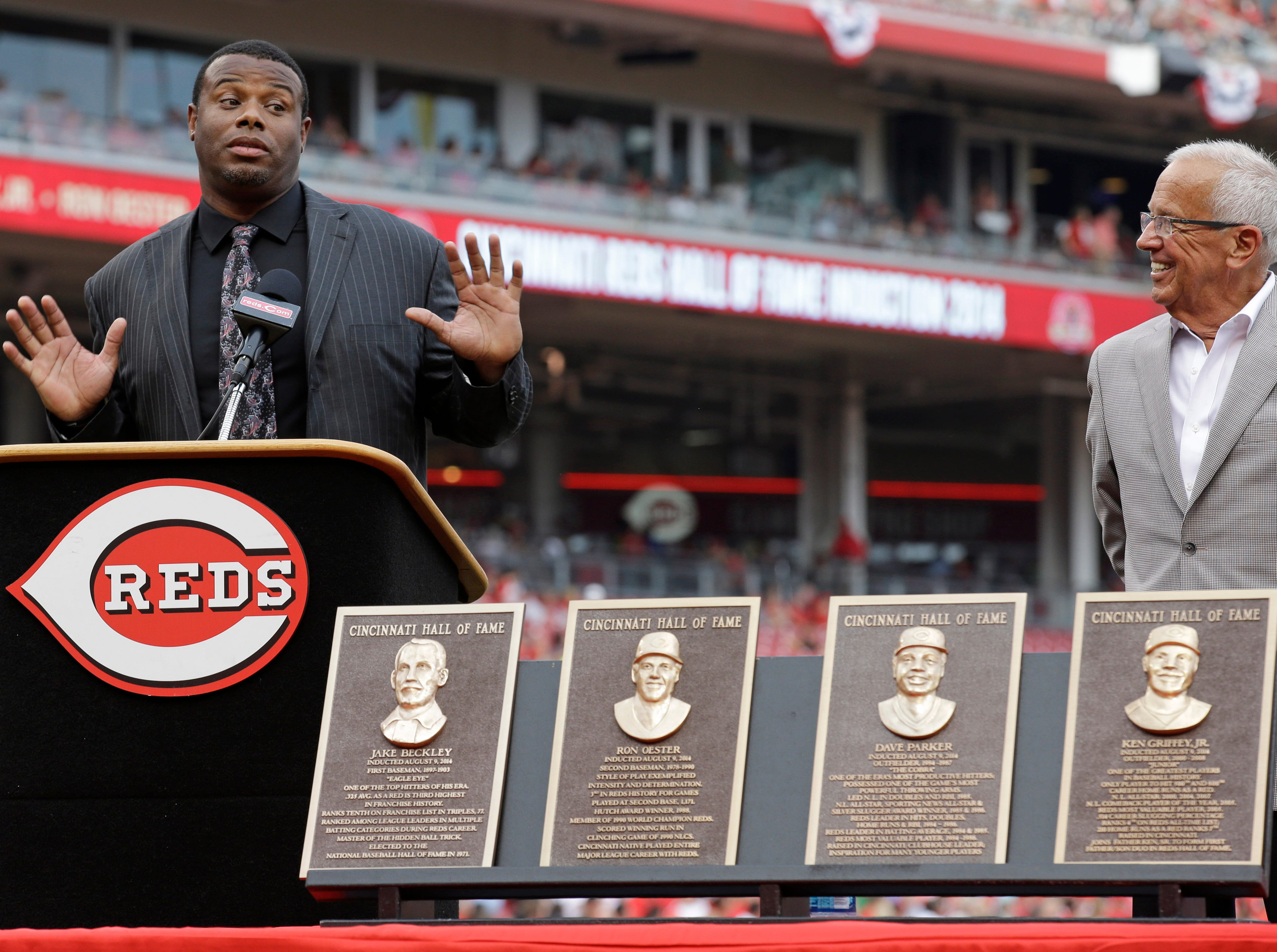 Former Cincinnati Reds player Ken Griffey Jr. speaks as he was inducted into the Reds Hall of Fame, Saturday, Aug. 9, 2014, prior to team's baseball game against the Miami Marlins in Cincinnati. Reds broadcaster Marty Brennaman listens at right.