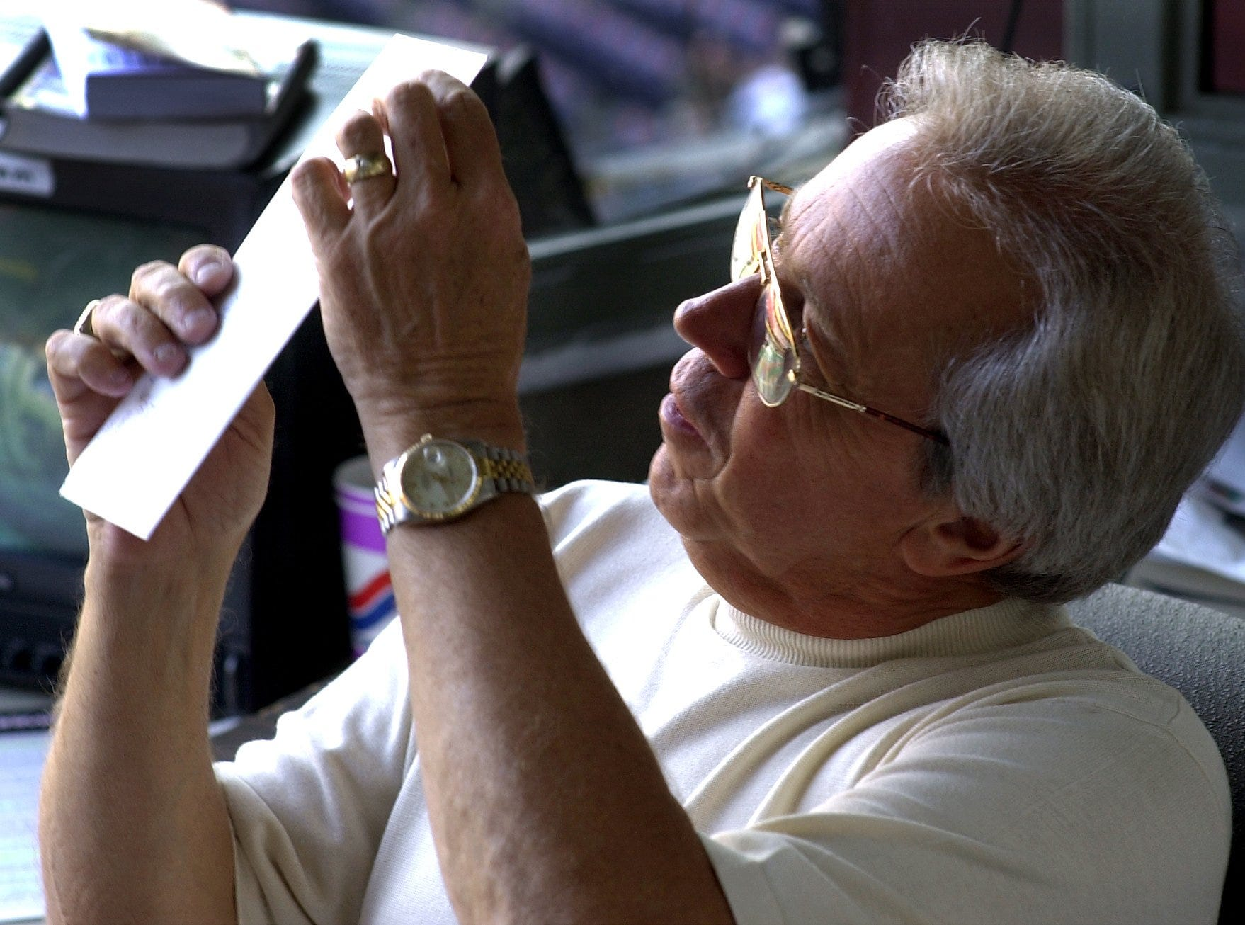 Text: 2000.0628.10.1--MARTY BRENNAMAN--nikon digital image--Marty Brennaman looks through his fan mail before the Reds-Cardinals game Wednesday.