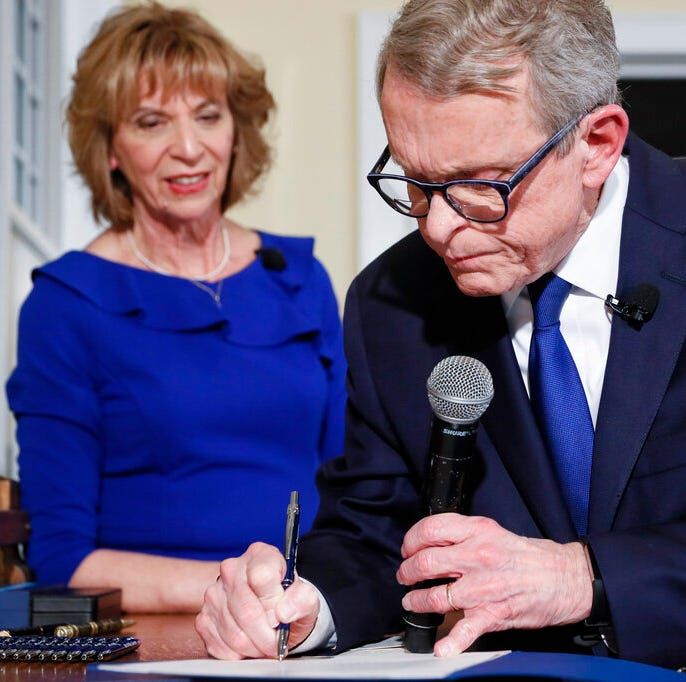 Ohio Gov. Mike DeWine signs one of six executive actions alongside his wife Fran, left, Monday, Jan. 14, 2019, in Cedarville, Ohio. The former U.S. senator took his oath in a private midnight ceremony at his Cedarville home ahead of a public inauguration planned Monday at the Statehouse.