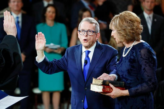 Ohio Governor Mike DeWine takes the oath of office alongside his wife Fran during a public inauguration ceremony at the Ohio Statehouse, Monday, Jan. 14, 2019, in Columbus, Ohio. (AP Photo/John Minchillo, Pool)