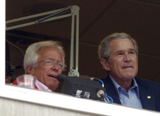 President George W. Bush sits in the broadcast booth with Cincinnati Reds broadcaster Marty Brennaman, left, during the Reds baseball game with the Chicago Cubs, Monday, April 3, 2006, in Cincinnati.