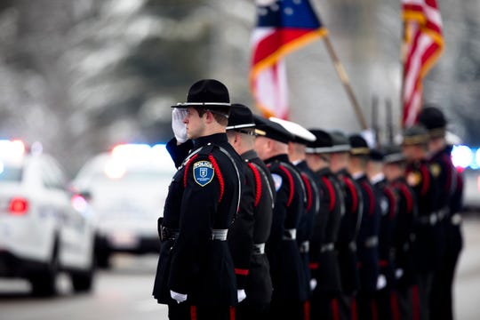 Members of the color guard salute during the procession for Colerain Police Officer Dale Woods from Spring Grove Funeral Homes to the Cintas Center on Monday, January 14, 2019. Dale Woods, 46, died Jan. 7  after being hit by a pickup truck Jan. 4 while working at the scene of a crash.