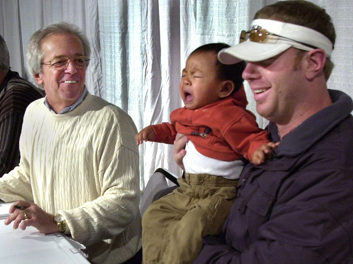 Text: 2002.0125.10.1--REDS CARAVAN--Adam Dunn holds Ethan Daniels, 15 months, of Lima, Ohio while they pose for a photo for Ethan's parents, although the boy was a little cranky as Marty Brennaman smiles at a stop in Lima, Ohio, as a small group of the Cincinnati Reds headed out on a tour bus for a three state trip. The Reds Caravan brings players, front office staff and other Reds organization members in contact with the public. Photo by Craig Ruttle/Cincinnati Enquirer