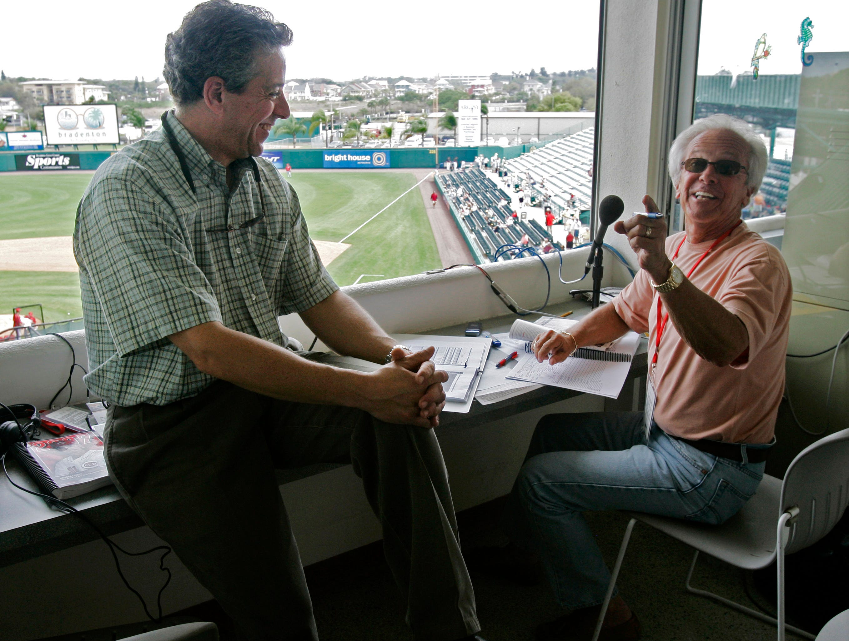 Cincinnati Reds broadcasters Thom Brennaman, left, and his father, Marty Brennaman, joke in the broadcasting booth prior to a spring training baseball game against the Pittsburgh Pirates, Thursday, March 1, 2007, in Bradenton, Fla. The two were doing their first Reds broadcast together.