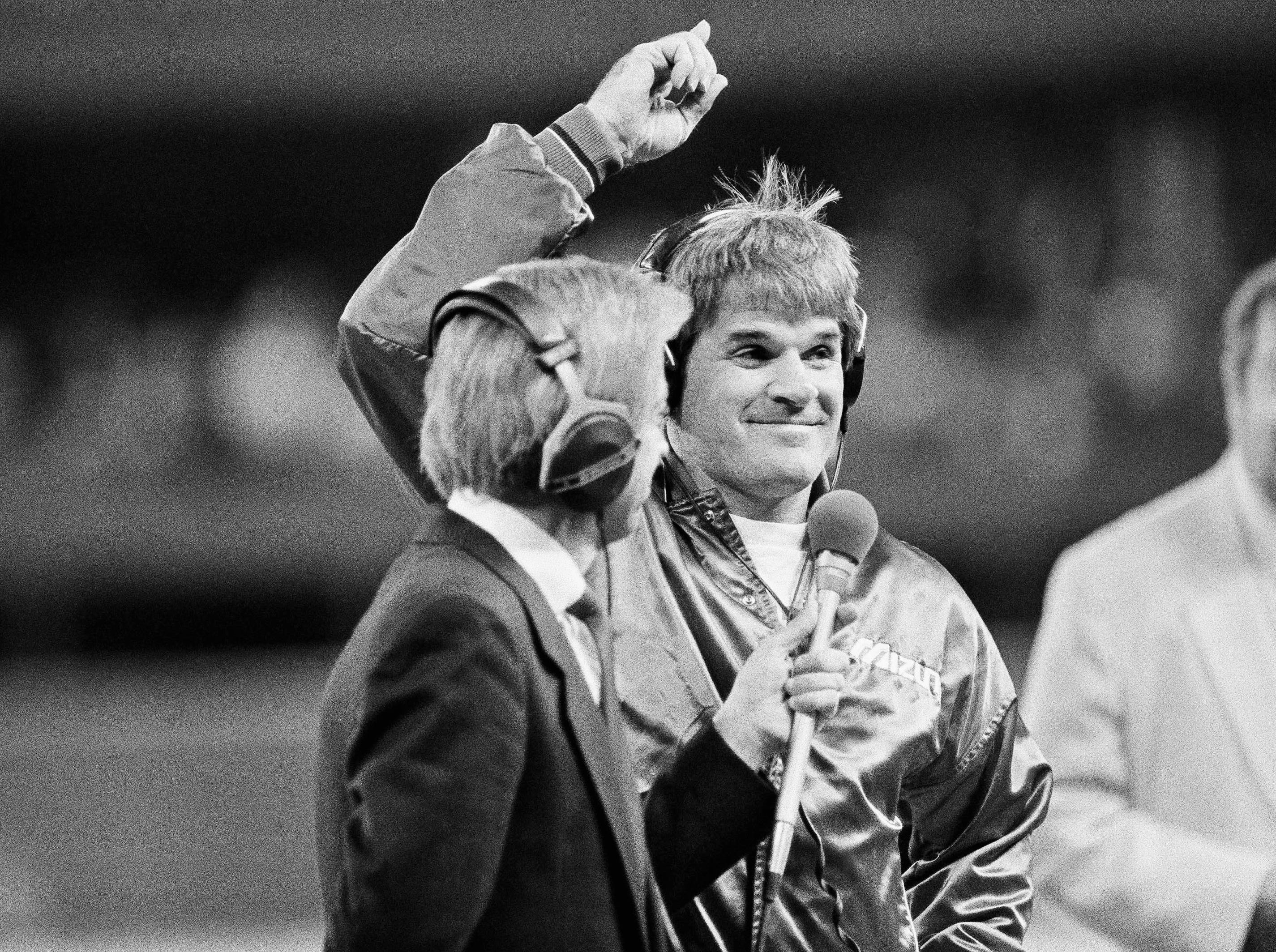 Cincinnati Reds player-manager Pete Rose signals to the crowd as President Reagan talks with him via telephone hookup, Wednesday, Sept. 11, 1985 in Cincinnati. Rose singled in the first inning to break Ty Cobb's all-time hit record. Reds radio announcer Marty Brennaman handles the mike.
