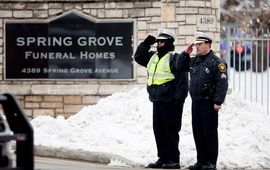 Police officers salute during the procession for Colerain Police Officer Dale Woods from Spring Grove Funeral Homes to the Cintas Center on Monday, January 14, 2019. Dale Woods, 46, died Jan. 7  after being hit by a pickup truck Jan. 4 while working at the scene of a crash.