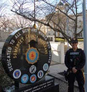 Special response team member, Officer Karissa Hahn stands near one of the monuments at the Veterans Memorial Plaza in Somerville.
