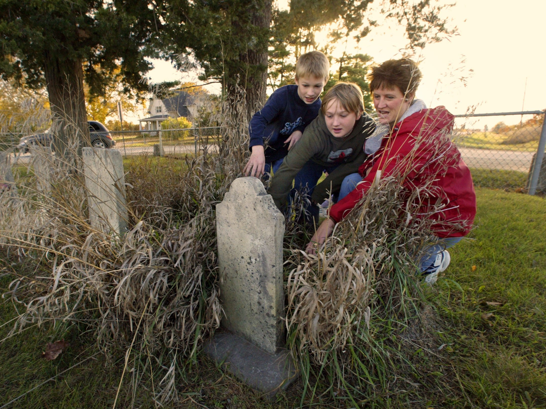 From 2004: Stephanie Watson and her sons, Jeremy, 8, left, and Carter, 11, check out old headstones at the Huston Cemetery near their home. The pioneer cemetery is in the middle of the intersection of 88th Street and Mills Civic Parkway in Dallas County, just minutes from Jordan Creek Town Center.
