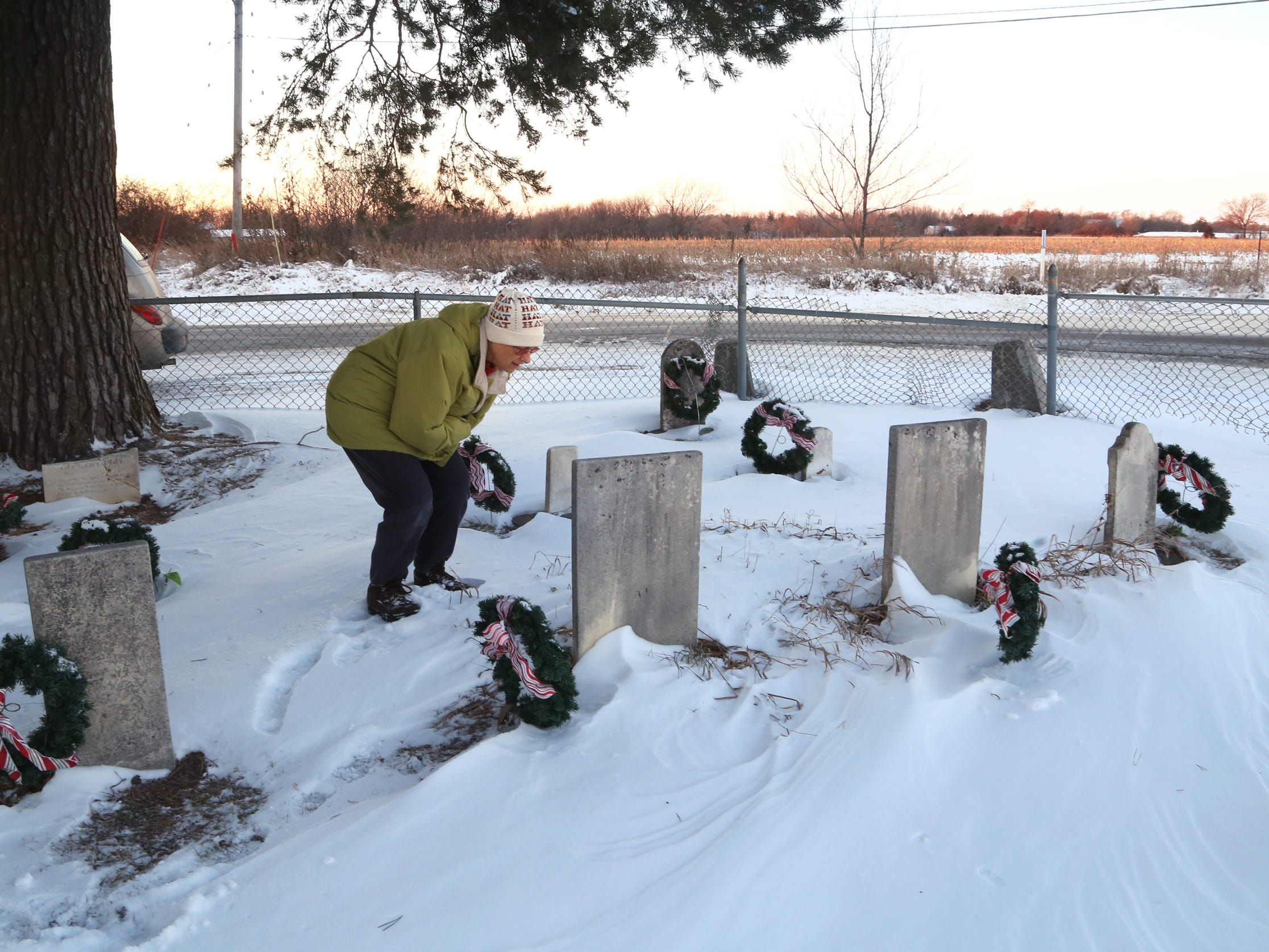 From 2013: Members of the Huston's Plot chapter of The Questers care for the tiny Huston Cemetery, located in the middle of Mills Civic Parkway in Dallas County. Flo Dietz, shown here, and other members have placed wreaths and decorated the cemetery for various holidays.