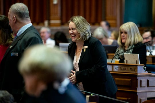 Newly elected Rep. Jennifer Konfrst, D-Windsor Heights, laughs from her desk on the first day of the 2019 legislative session on Monday, Jan. 14, 2019, at the Iowa State Capitol in Des Moines.