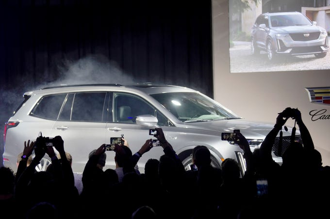 Journalists reach to take photos of the 2020 Cadillac XT6, a new three-row SUV, at the Garden Theater during the North American International Auto Show in Detroit on Sunday, Jan. 13, 2019.