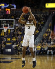 Michigan guard Zavier Simpson hits a 3-pointer against Northwestern during the first half Sunday at Crisler Center.