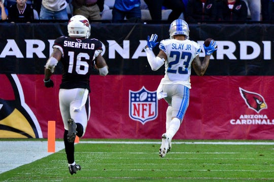 Lions cornerback Darius Slay returns an interception for a touchdown as Cardinals receiver Trent Sherfield watches during the second half of the Lions' 17-3 win on Sunday, Dec. 9, 2018, in Glendale, Ariz.