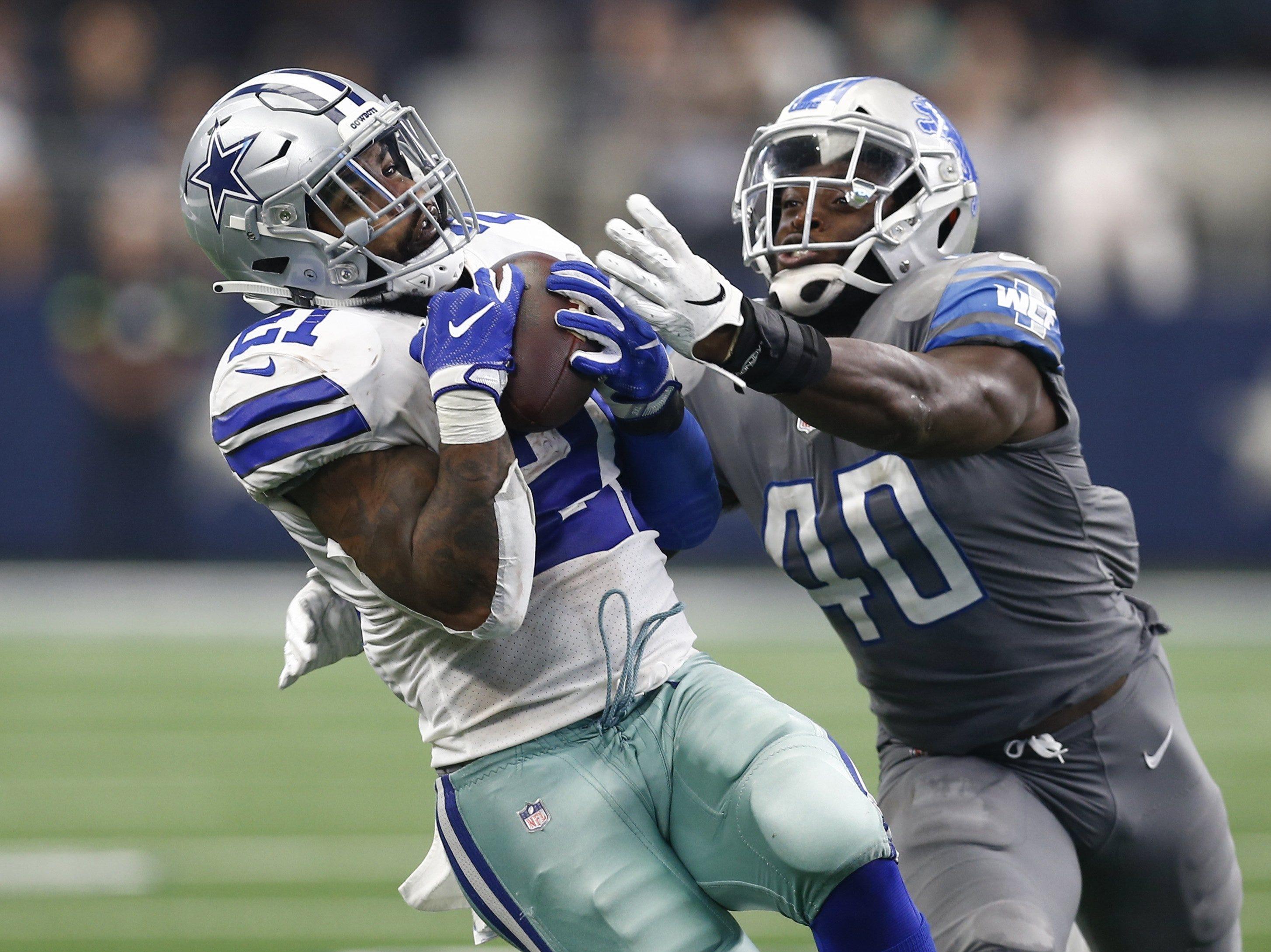 Cowboys running back Ezekiel Elliott hauls in a pass in front of Lions linebacker Jarrad Davis in the fourth quarter of the Lions' 26-24 loss on Sunday, Sept. 30, 2018, in Arlington, Texas.