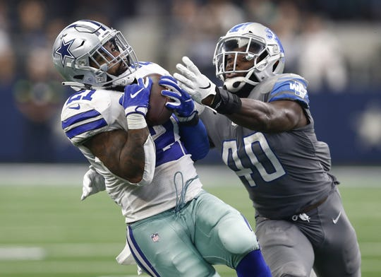 Cowboys running back Ezekiel Elliott hauls in a pass in front of Lions linebacker Jarrad Davis in the fourth quarter of the Lions' 26-24 loss on Sunday, Sept. 30, 2018, in Arlington, Texas.