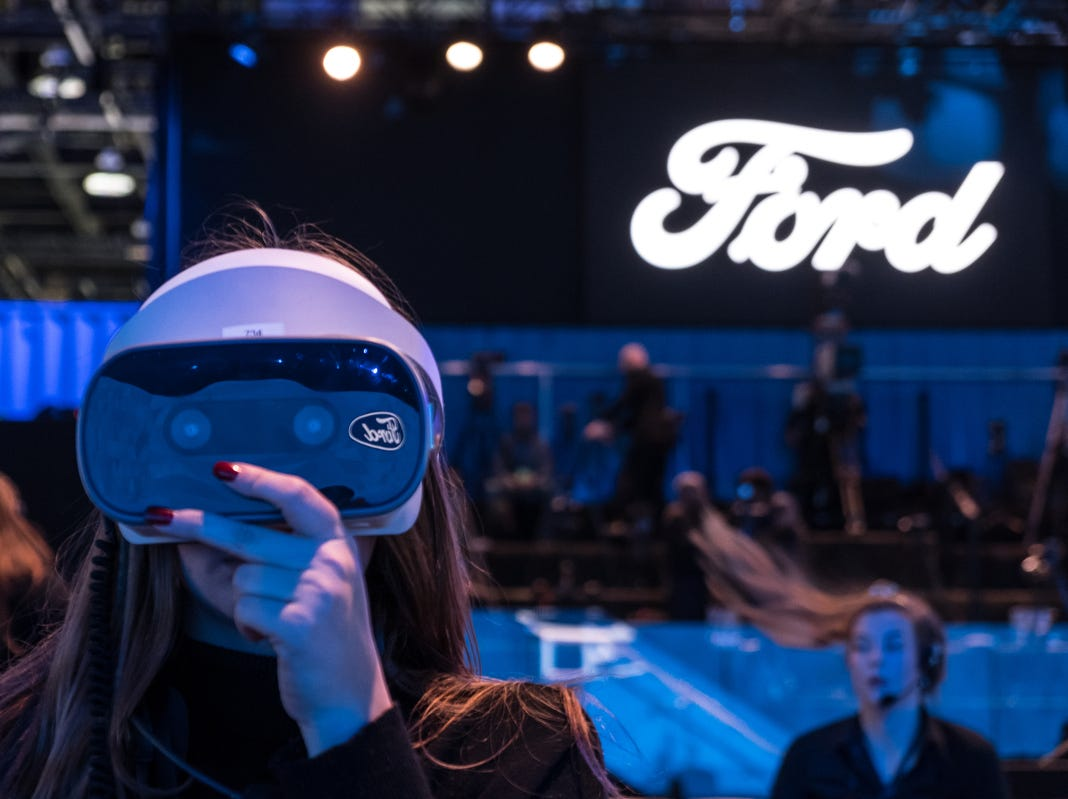 A woman adjusts VR headsets for the start of a reveal for Ford Motor Co. during the 2019 North American International Auto Show held at Cobo Center in downtown Detroit on Monday, Jan. 14, 2019.