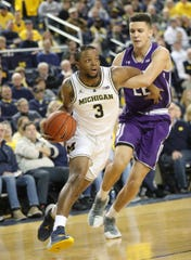 Zavier Simpson drives against Northwestern's Pete Nance Jr. on Sunday in Ann Arbor.